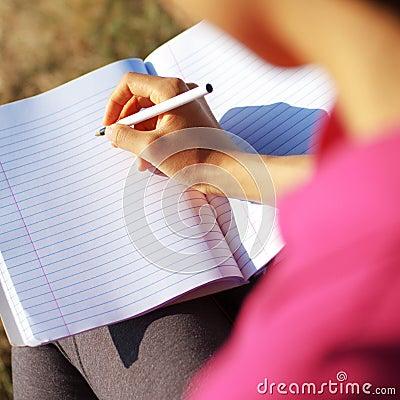 Escritura de la muchacha en cuaderno