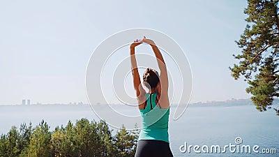 Esercitazione mattutina all'aperto sullo sfondo della città una ragazza su un'altissima riva fa allenamento stock footage