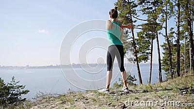 Esercitazione mattutina sulla riva del fiume Una ragazza che fa il corpo stirandosi prima dell'addestramento video d archivio