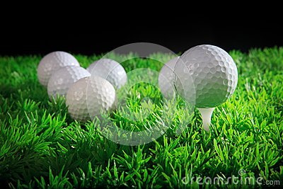 Esfera e T de golfe na grama verde