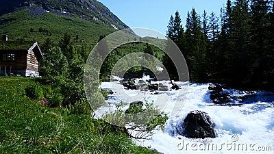 Esfregando rapidamente a água branca em consequência do derretimento de neve na montanha da Noruega Belo rio rochoso ruindo por b video estoque