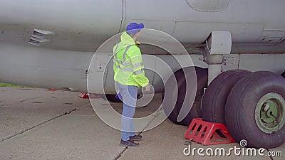 Especialista efetua uma verificação técnica do quadro de uma aeronave de passageiros no aeroporto filme