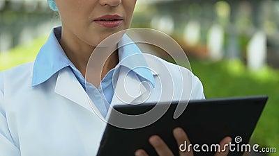 Especialista en biología femenina trabajando en tableta en línea, investigación ecológica metrajes