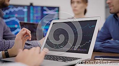 Especialista financeiro está vendo gráficos na tela do laptop, folheando fotos na reunião de negócios na sala de escritórios video estoque