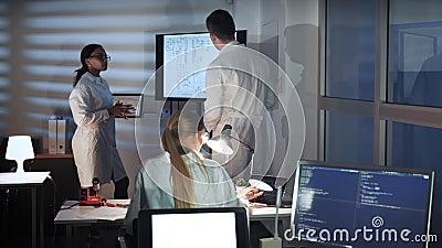 Especialistas multirraciales en electrónica que hablan algo y que muestran en una pantalla grande de la TV en laboratorio almacen de video