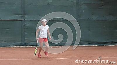 Esporte profissional, menina adolescente do jogador de tênis que concentra-se e que centra-se sobre o jogo que bate então a raque filme