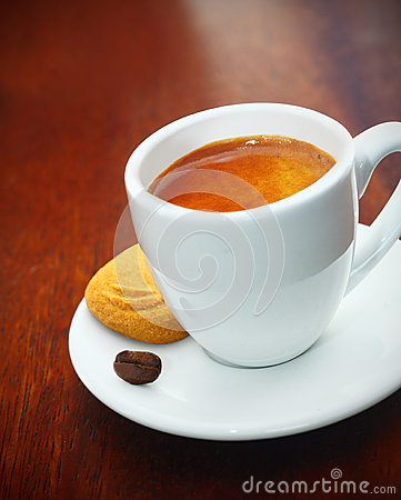 Espresso coffee served with a biscuit