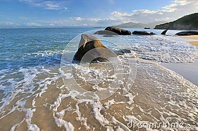 Espuma e rocha da água de mar na iluminação do por do sol