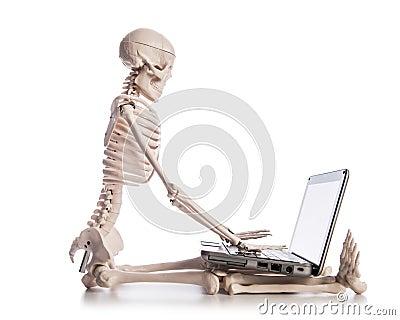 Esqueleto que trabaja en la computadora portátil