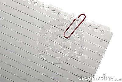 Esquina del papel de nota en blanco con el paper-clip rojo.