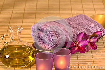 Essential oil, candles, towel and purple flowers.