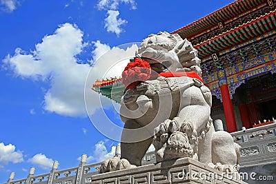 Estátua chinesa do leão contra o céu azul