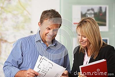 Estado femenino que discute a los detalles con el cliente