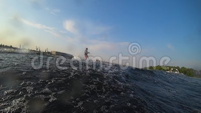 Estilo de vida extremo, o desportista viaja a bordo atrás de um barco a motor no rio e faz salpicos de água na lente da câmera du video estoque