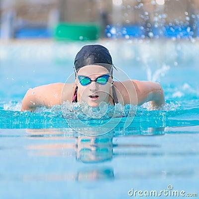 Estilo del movimiento de mariposa de la natación de la chica joven
