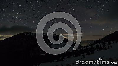 Estrelas e nuvens que movem-se no céu noturno sobre montanhas do inverno Lapso de tempo sonhador da astronomia video estoque