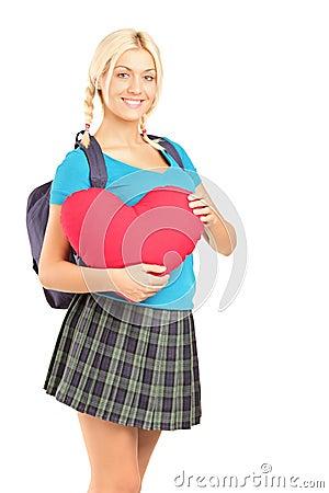 Estudante bonito que prende um objeto da forma do coração