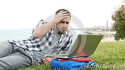 Estudante triste verificando notas on-line com um laptop filme