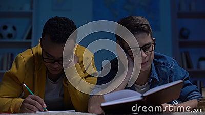 Estudantes adolescentes sobrecarregados que sentem a falta da energia preparar-se para o exame tarde na noite video estoque