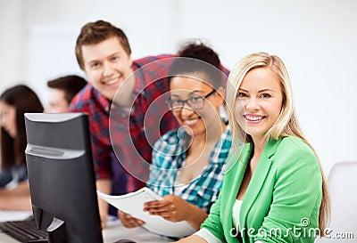 Estudantes com computador que estudam na escola