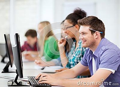 Estudantes com computadores que estudam na escola