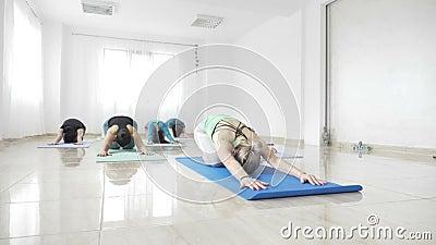 Estudantes de mulheres que dão certo sua flexibilidade em uma esteira durante uma classe da ioga no movimento lento - vídeos de arquivo