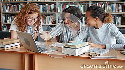 Estudantes meninas e caras trabalhando em projeto na biblioteca usando laptops e livros video estoque
