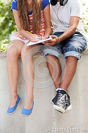 Estudantes que sentam-se com livro