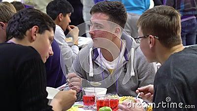 Estudantes que têm o almoço na sala de jantar vídeos de arquivo