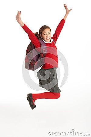 Estudiante femenino feliz en el uniforme que salta en aire
