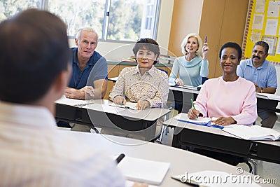 Estudiante femenino maduro que levanta la mano en clase