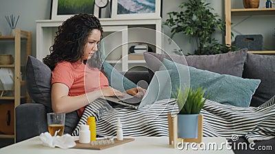 Estudiante malsano que usa el ordenador portátil que tose la medicina de consumición en casa almacen de video