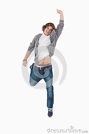 Estudiante masculino que presenta saltando con un brazo levantado
