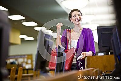 Estudiante universitario de sexo femenino que cuelga hacia fuera en biblioteca