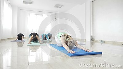 Estudiantes de mujeres que resuelven su flexibilidad en una estera durante una clase de la yoga en la cámara lenta - almacen de metraje de vídeo
