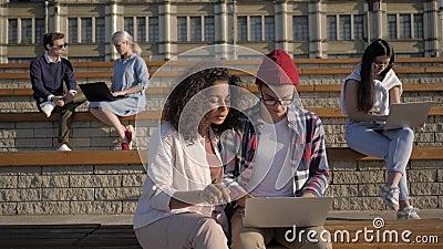Estudiantes haciendo proyectos en laptops fuera de la universidad almacen de video
