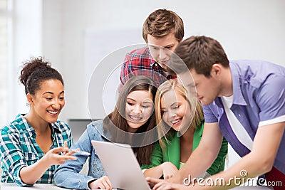 Estudiantes internacionales que miran el ordenador portátil la escuela