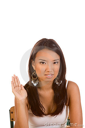 Ethnic Asian student with raised hand by desk