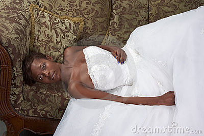 Ethnic black woman bride wedding dress on couch