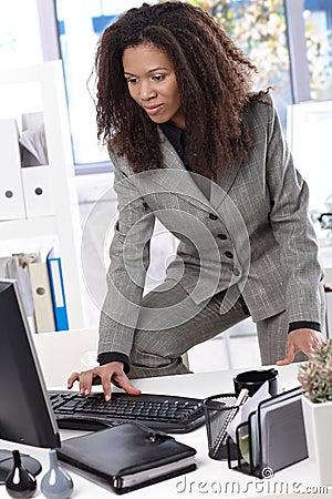 Ethnic businesswoman typing on keyboard