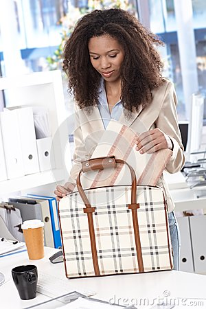 Ethnic businesswoman unpacking bag at office