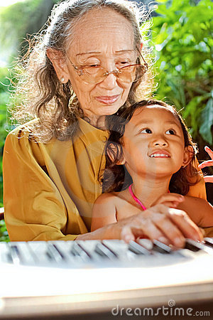 Ethnic child and grandmother playing piano