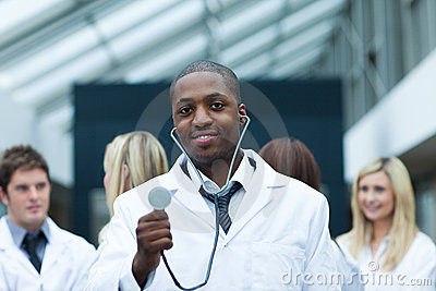 Ethnic doctor with his team in the background