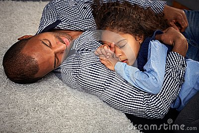 Ethnic father and little girl sleeping on floor