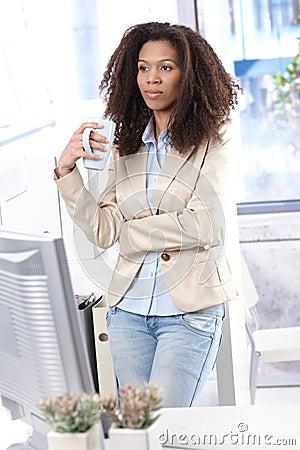 Ethnic office worker drinking tea in office