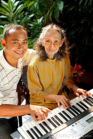 Ethnic old mother and son happy playing piano