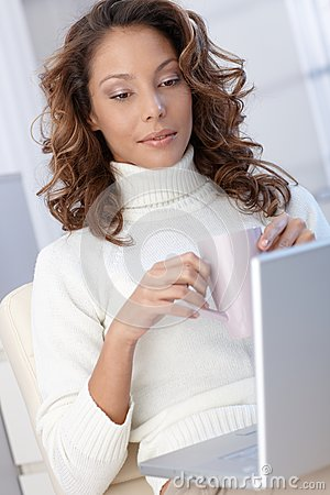 Ethnic woman with computer a home