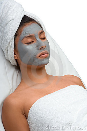 Ethnic woman relaxing during facial in spa