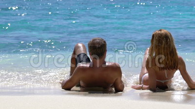 Ett älska par som tycker om semester på en tropisk strand långsam rörelse stock video