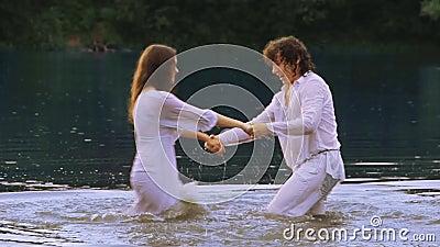Ett älska plaskande vatten för par i en sjö i sommar stock video
